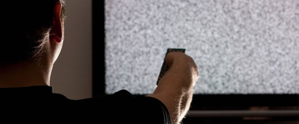 A man pointing a remote at a TV showing static