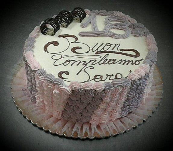 Torta di compleanno con decorazioni rosa e viola