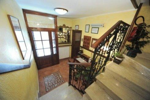 scala con scorrimano in legno e ferro battuto, vasi con delle piante e visuale dall'alto di una porta di legno