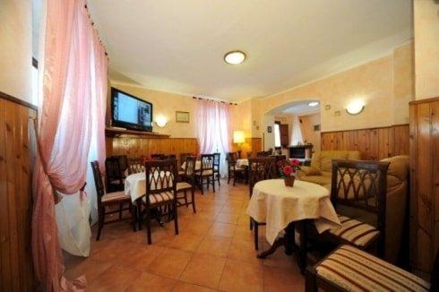 sala con tavoli, sedie di legno, due poltrone arancioni, tv e una tenda rosa sulla destra