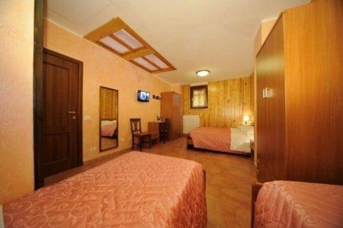 camera da letto con due letti singoli con copriletto rosa uno vicino all'altro, al centro un armadio in legno e in fondo un altro letto singolo