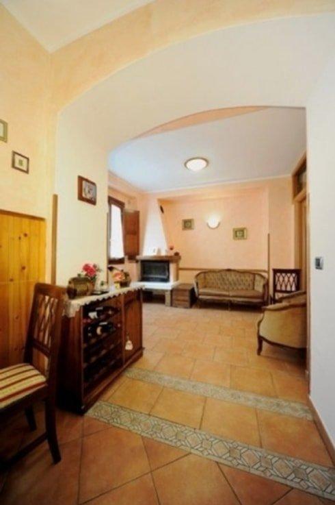 stanza con sulla sinistra una sedia, un mobiletto marrone con sopra un vaso di fiori rosa e di fronte due divanetti color beige