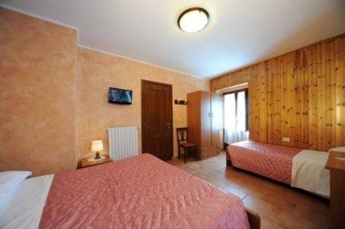 stanza con due letti uno matrimoniale e uno singolo con copriletti rosa, si vede un armadio, un comodino con una lampada e un calorifero