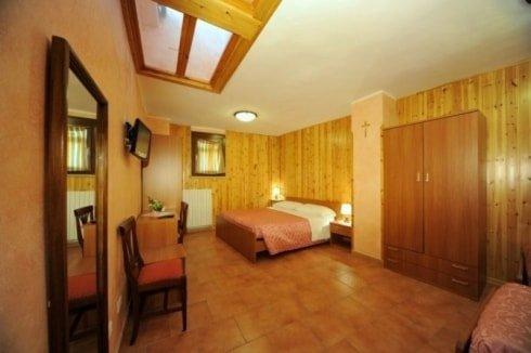 stanza con specchiera sulla sinistra, una sedia,sopra una tv affissa al muro, armadio di legno e letti separati quasi a formare due camere