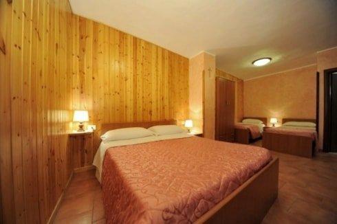 camera con letto matrimoniale, sulla sinistra un comodino con una lampada e sulla destra due letti singoli