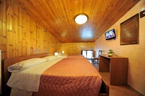 stanza con letti matrimoniali separati sulla sinsitra e di fronte una tv e una scrivania in legno