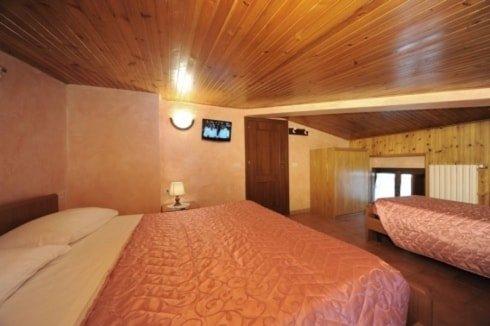 stanza con letto matrimoniale sulla sinistra tv a muro con sotto un comodino con una lampada e sulla destra un letto singolo