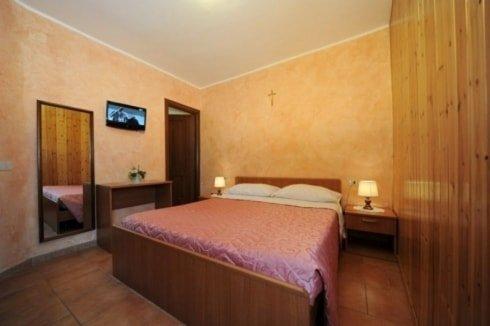 camera con letto matrimoniale, sulla destra comodino con lampada e sulla sinistra una specchiera, una tv a muro e una scrivania con sopra un vaso di fiori