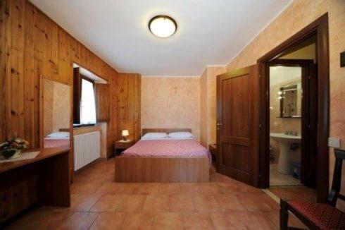 stanza con al centro letto matrimoniale, sulla sinistra un calorifero, una specchiera, una scrivania con dei fiori, sulla destra si intravede una sedia e la porta del bagno semiaperta con vista del lavabo