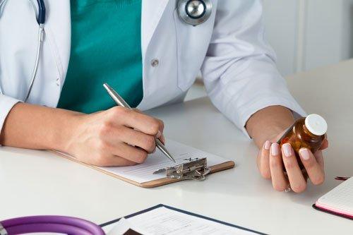 una farmacista con in mano un flacone con un medicinale mentre scrive su un documento