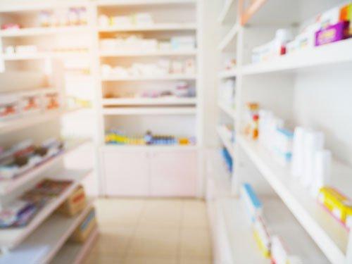 degli scaffali con dei farmaci all'interno di una farmacia