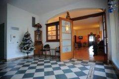 sala con pavimento a quadri e porta aperta su un'altra stanza