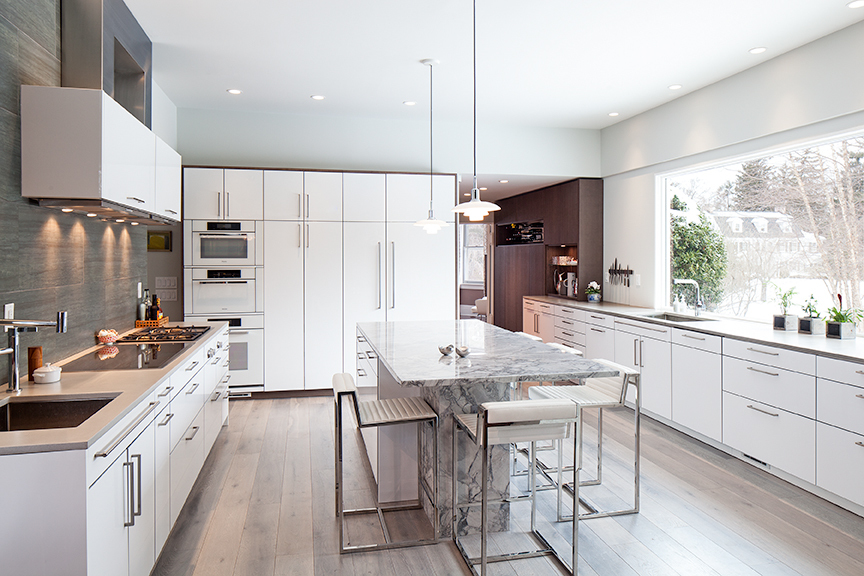 Picture of Montclair kitchen renovation featuring white stained wood flooring, bright, white lacquer cabinets, marble island with seating, double vent hood over range