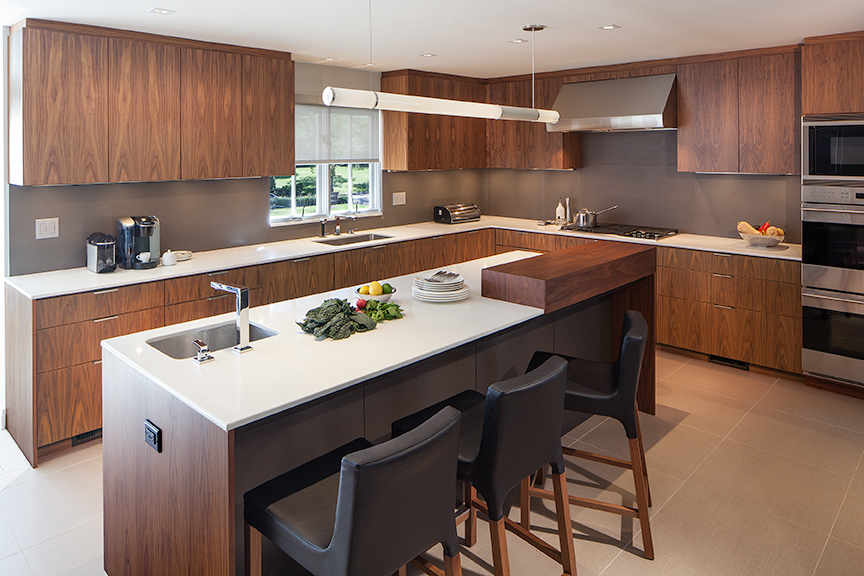 Modern residential architecture. Walnut kitchen with quartz counters and porcelain tile backsplash.