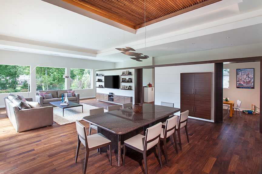 Modern residential architecture. This great room space was the primary addition to the existing house. The dining area is capped by a walnut strip recessed ceiling.  The large custom cabinetry houses various types of storage and provide separation for a play area for the kids.