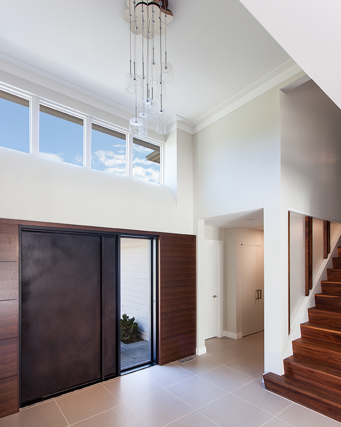 Modern residential architecture. The new steel door and sidelight is surrounded by walnut panelling. New stairs lead to existing bedrooms.