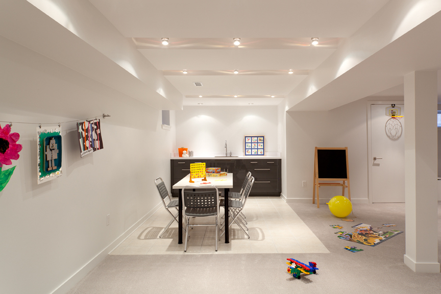 Modern residential architecture. Recessed track lighting set between the floor structure above adds dimension to this bright basement play area.