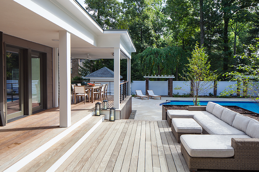 Modern residential architecture NJ. The covered deck provides protection from the summer sun.  The expanded seating area overlooks the pool and can be transformed into a screened in porch at the touch of a switch.