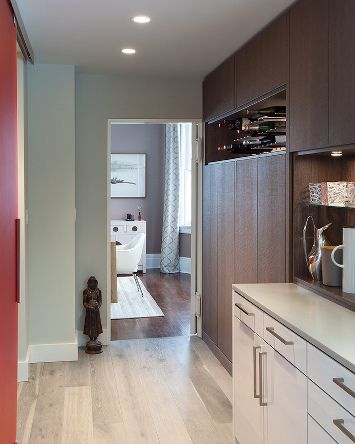 Modern residential architecture. The pantry area connects the dining room to the kitchen. A translucent, red resin sliding door leads to the new laundry room and  provides a colorful  accent to the neutral tones used elsewhere.