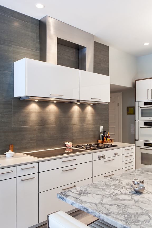 Modern residential architecture. Two cooktops, each with their own exhaust hood. The location of existing structure above led to the solution of the combined stainless steel duct covers.