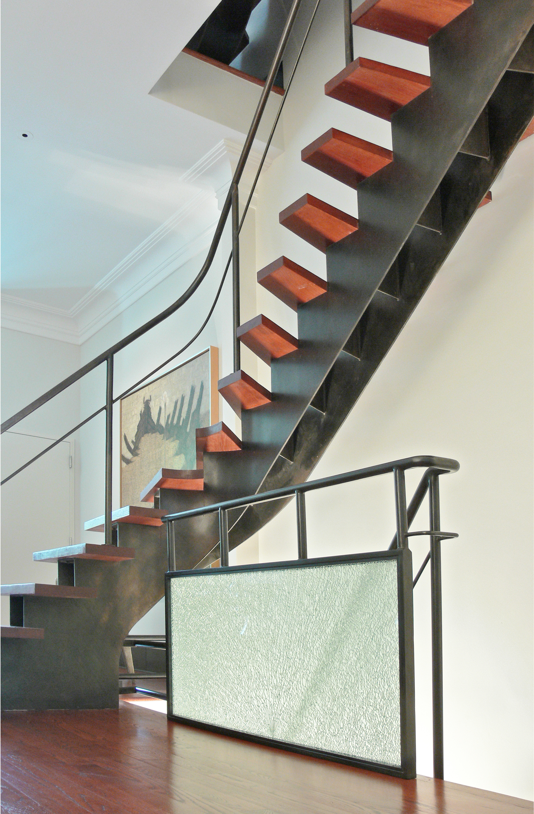 Modern residential architecture. The original stair was replaced with this sculptural blackened steel version. Shattered glass panel in the railing provides an unexpected textural complement.