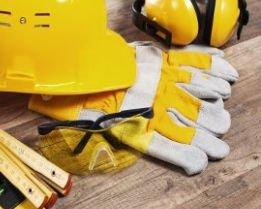 un casco antinfortunistico di color giallo, delle cuffie e dei guanti