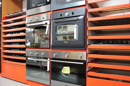 esposizione di forni e accanto in scaffali con piccole mensole arancioni dei piani cottura