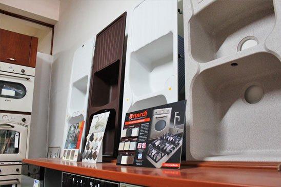 un banco in legno e sopra affissi al muro un' esposizione di lavandini da cucina