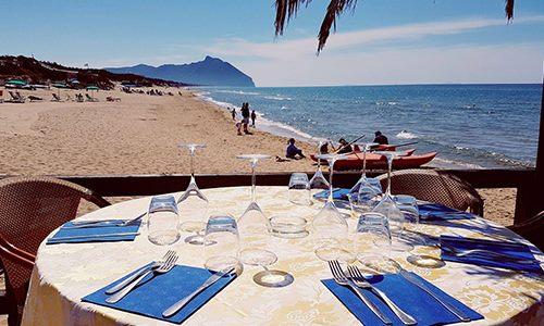 un tavolo apparecchiato e vista di una spiaggia e del mare