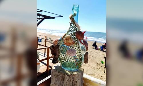 una bottiglia di vetro con una rete e delle conchiglie