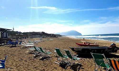 una spiaggia con sdraio, pedalò e vista del mare