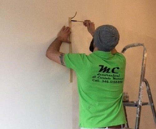 Pittore che decora una parete