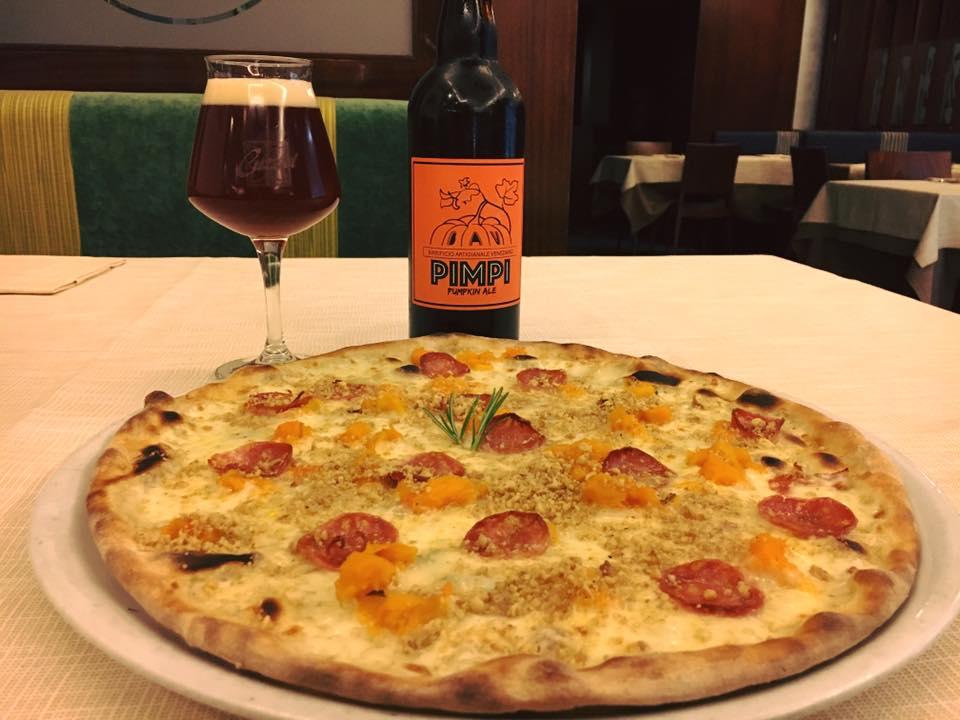una pizza con pomodorini freschi,una  bottiglia e un bicchiere