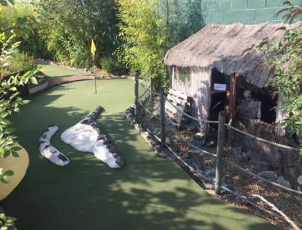 A putting green in front of a battered old barn behind an iron fence