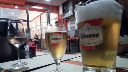 un banco con un bicchiere di vino e dei boccali di birra