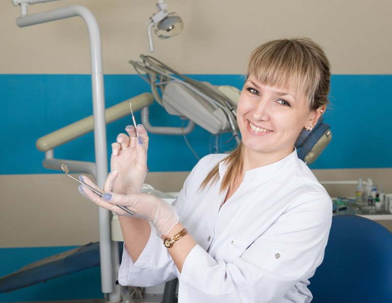 dentist smiling and displaying her tools