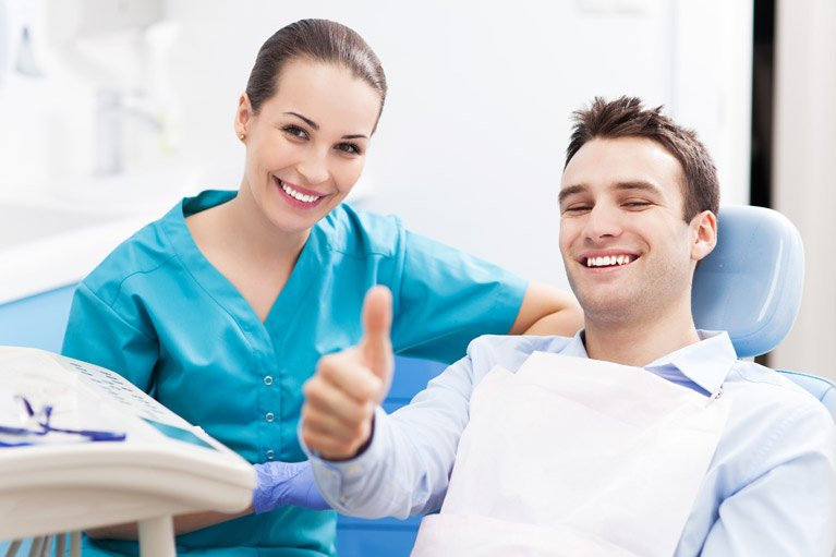 dental patient giving the thumbs-up