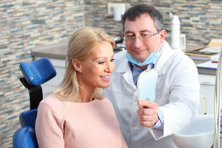 dentist holding a mirror for patient