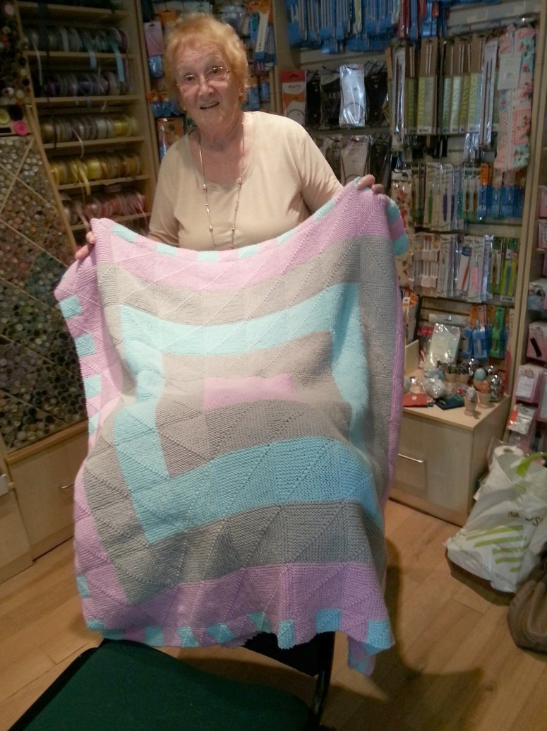 A lady holding a quilt