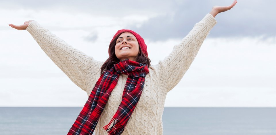 A lady in a white aran jumper, red beanie hat and red tartan scarf, standing with her arms up and her back to the sea