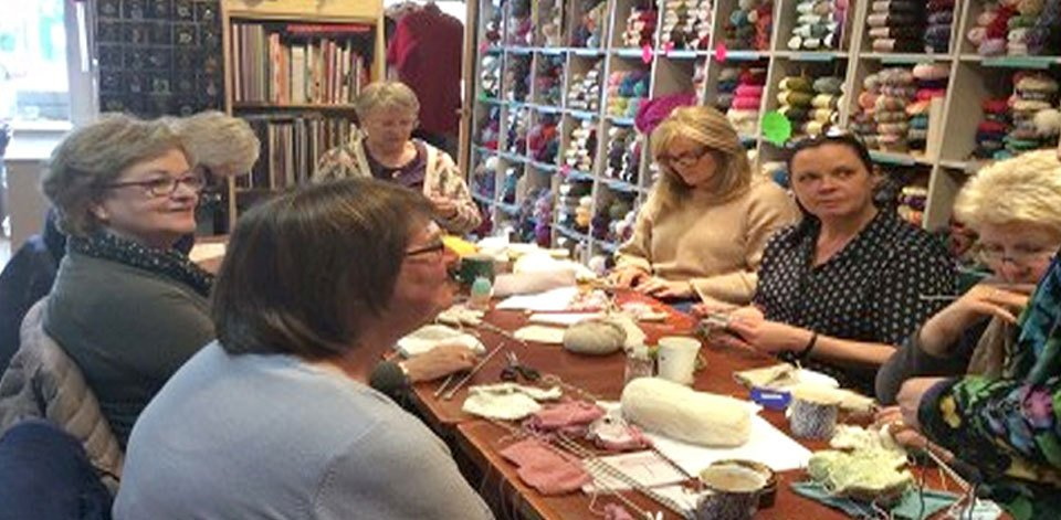 A knitting club group sitting around a large table in front of shelves of yarn and material