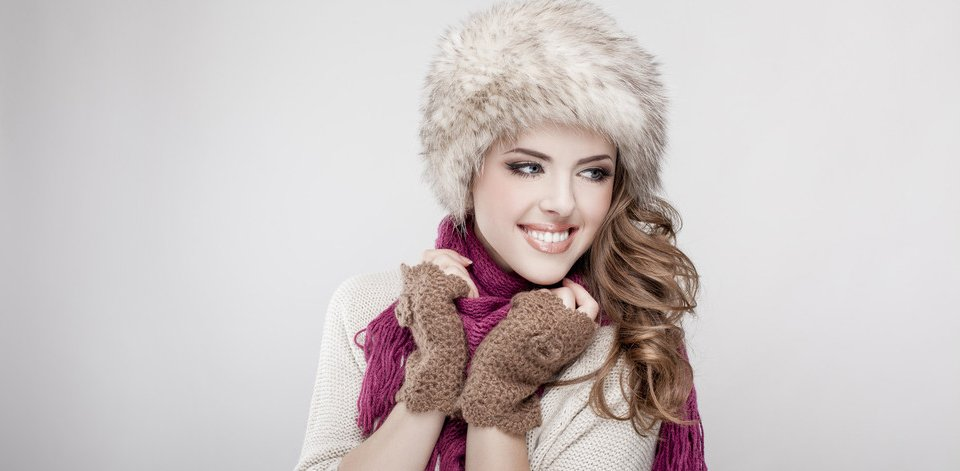 A young lady wearing a fur hat, chocolate brown fingerless gloves and purple scarf