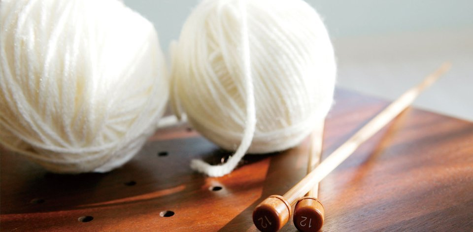 Knitting needles and two balls of white yarn on a wooden table