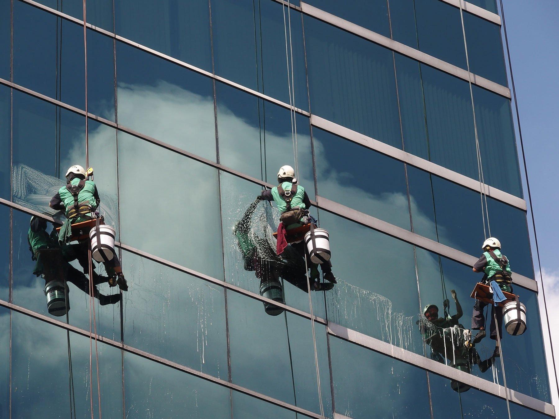 Degli operai puliscono delle finestre di un grande palazzo dall'esterno