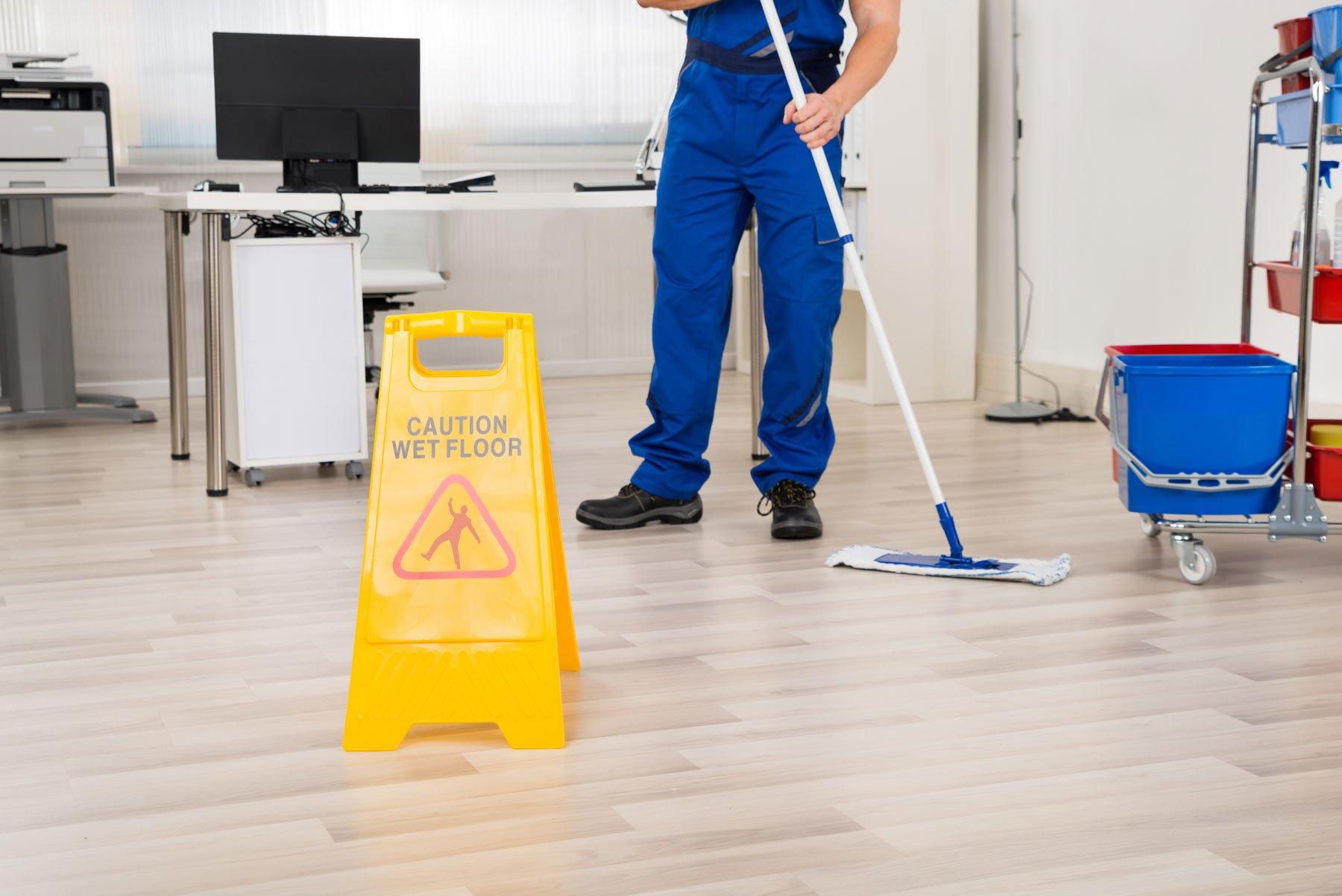 Un uomo pulisce un parquet con un cartello di attenzione per il pavimento bagnato