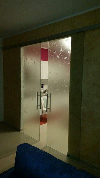 porta in vetro con disegni floreali semiaperta