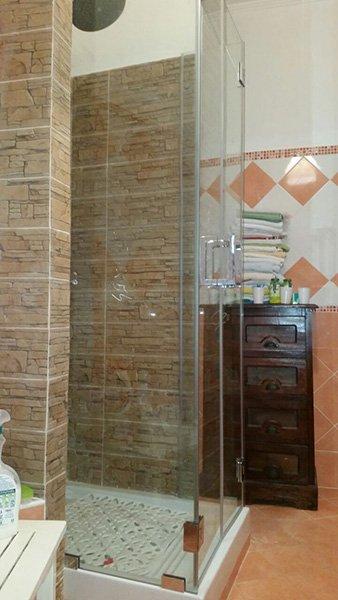 vetrata di un box doccia vista lateralmente, si vede anche una cassettiera in legno con sopra degli asciugamani