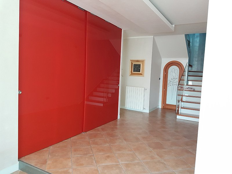 Anticamera con un armadio rosso laccato, un termosifone e delle scale che portano al piano superiore