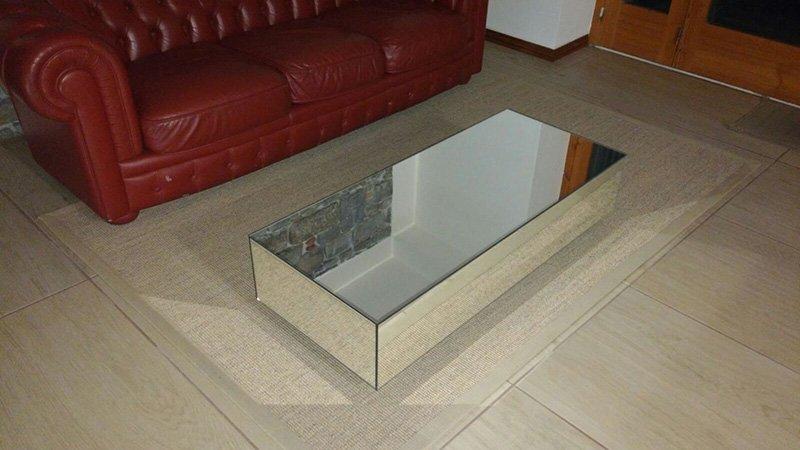 Tavolino in vetro e acciaio con vista di un divano bordeaux in pelle da un' angolazione diversa