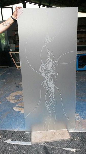 una mano mostra una lastra di vetro con una pianta disegnata